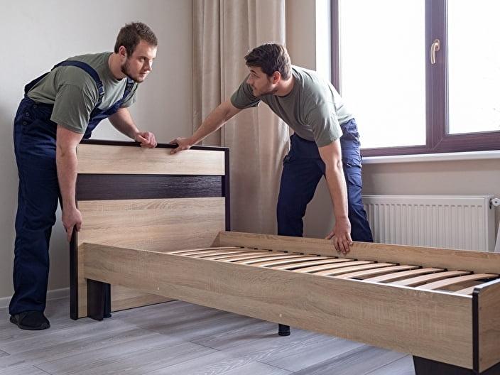 ベッドの処分をする男性2人