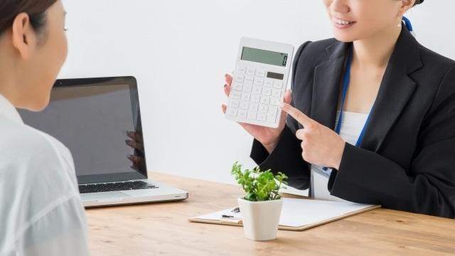 査定額を電卓で見せるスタッフ