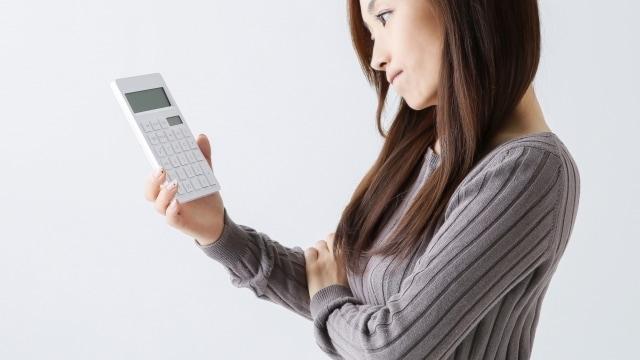 電卓を持ち悩む女性