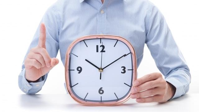 時計を示す男性